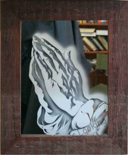 Praying hands etched onto mirror